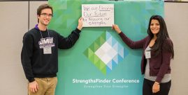 Image of of two students posing in front of a green StrengthsFinder Conference banner holding a sign that reads, 'We are elevating our future by knowing our strengths.'