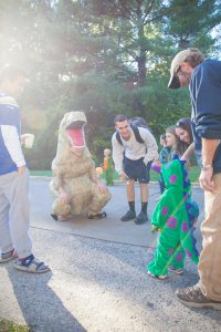 An adult and a child in dinosaur costumes meet outside.