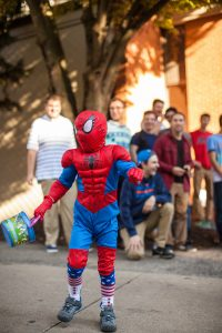 A child dressed up as Spiderman swings his bucket of candy around.