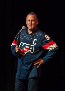 Dave Coulier stands on stage laughing.