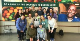 Image of students posing in front of a large poster that reads, 'Be part of the solution to end hunger.'