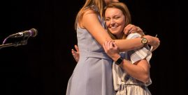 Image of two women hugging on stage