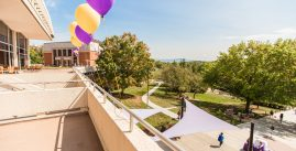 Image of the madison union patio, lined with purple and gold balloons, overlooking campus
