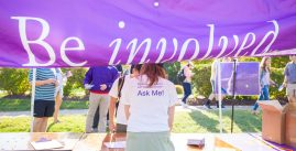 Image of a student standing at the Be Involved tent with a shirt that reads 'Questions about getting involved? Ask me!'