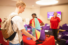 Student spinning a prize wheel at the Credit Union table