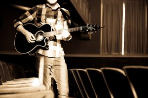 Musician holding acoustic guitar