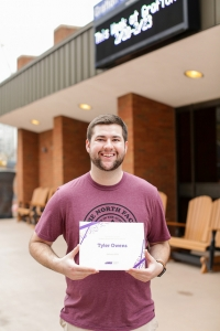Tyler stands in front of Grafton theater, with his employee of the month award