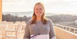 Image of Erica Winfrey with her employee of the month award on campus with a view in the background