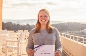 Erica with her employee of the month award on campus with a view in the background