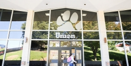 Image of a student entering the glass doors of Madison Union.