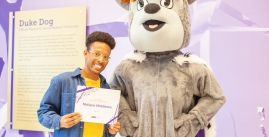 Image of Malique Middleton posing with the Duke Dog holding a certificate