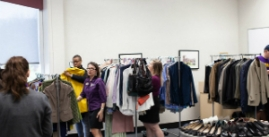 Image of four people looking through racks of clothing