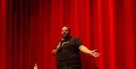 Image of Daniel Franzese with microphone in front of red curtain