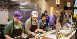 Image of four happy people serving breakfast food in a cafeteria line