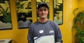 Image of Ben McCormick holding a certificate for Student Employee of the month