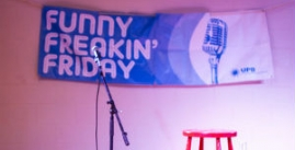 Image of a banner reading 'Funny Freakin' Friday' hanging behind a stool and microphone stand
