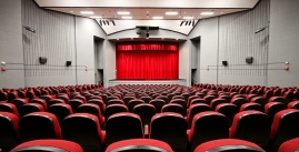image of theater with red chairs and red curtain