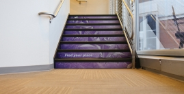 Image of A stairwell covered in purple geometric graphics.